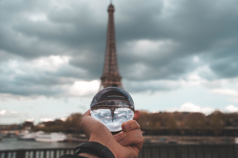 Man holding crystal ball with reflection of eiffel tower against cloudy sky
