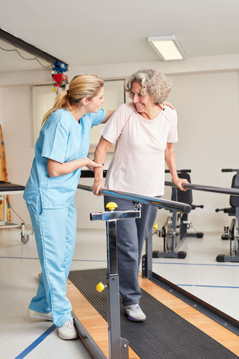 Nurse helping woman to exercise in gym