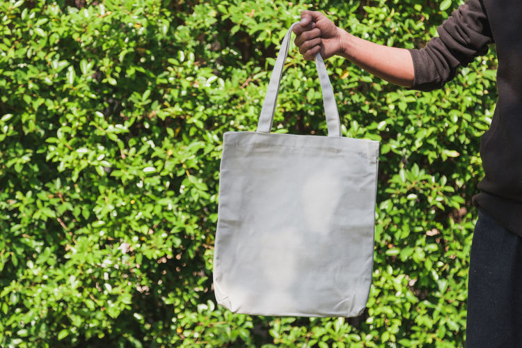 Midsection of man holding bag against plants