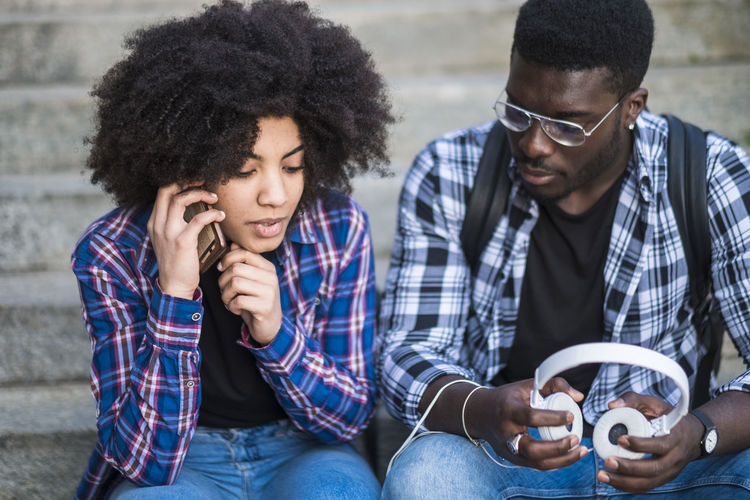 First date concept with diversity black race african hipster young couple using technology together enjoying the day - millennial girl and boy sitting - curly afro hair style - Young Adult Young Men Men Togetherness Sitting Adult Casual Clothing Two People Front View Holding Three Quarter Length Glasses Friendship Young Women People Looking Outdoors Couple - Relationship Checked Shirt Enjoying Life Millennial Beautiful People Music Listening To Music Eyeglasses  20-24 Years Sitting Staircase City Side View Sunlight City Life Enjoyment Technology Student Hipster - Person Freedom Jeans Relaxation Leisure Activity Arms Raised Hand Happiness Emotion Boyfriend Girlfriend