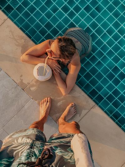 Low section of man standing by woman in swimming pool