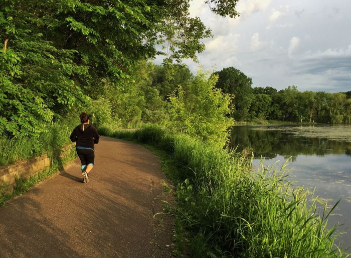 Full length of woman running on road by lake