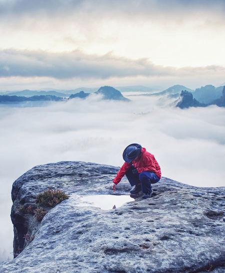 Nice hiker girl on mountain summit soak maple leaf in water eye pool.