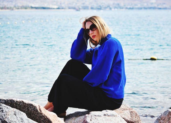 Woman Sitting On Rock By Sea