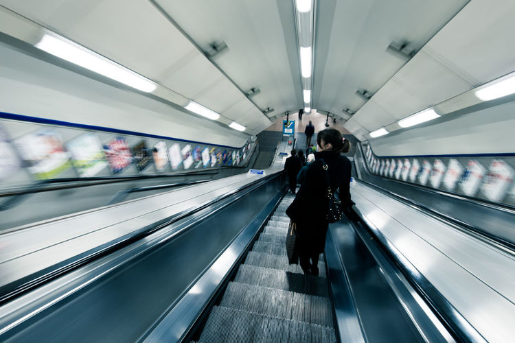 Rear view of people on escalators at subway station