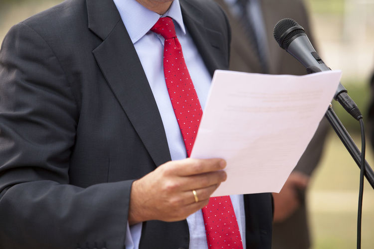 Midsection of businessman giving speech