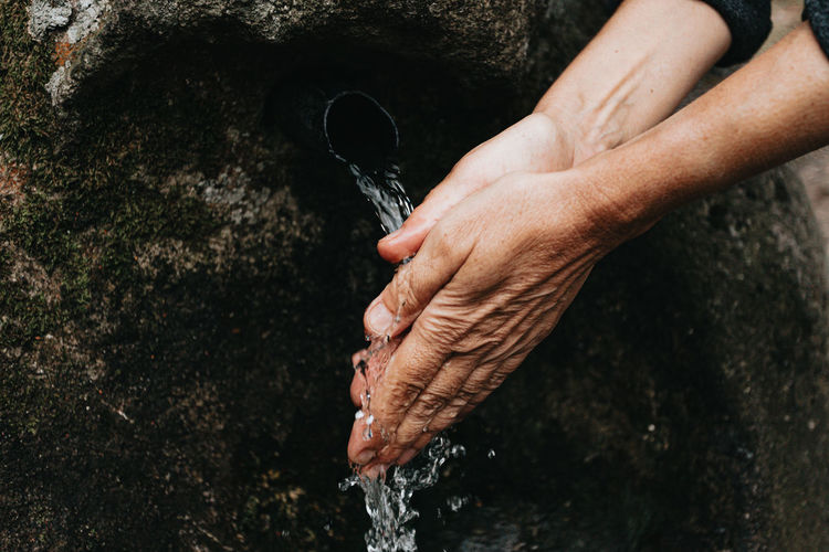 Cropped image of woman washing hand by running water
