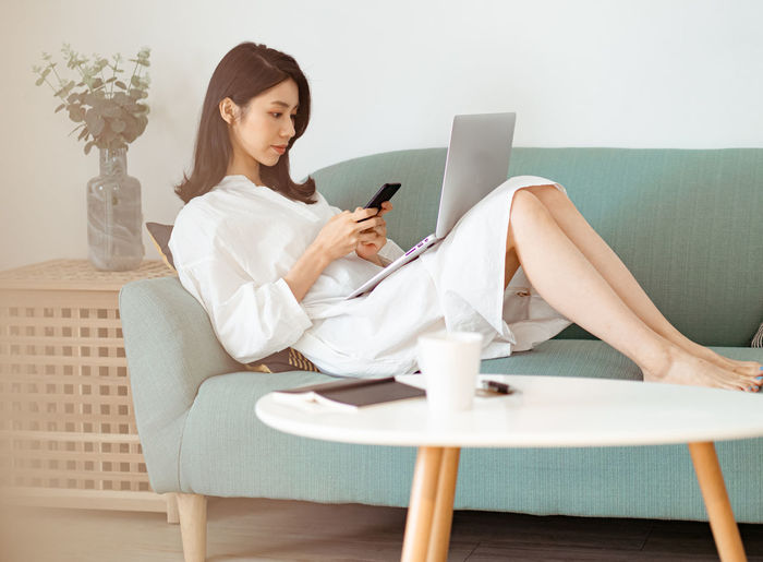 Young woman using mobile phone while sitting on sofa at home