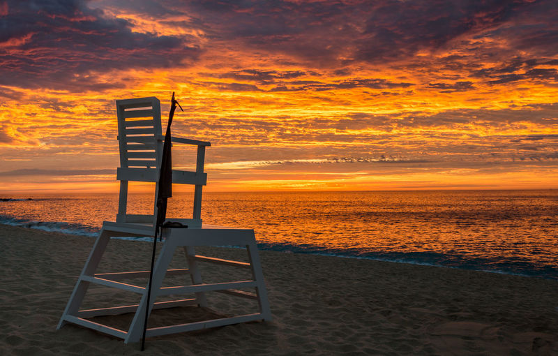 Lifeguard chair at beach against sky during sunset