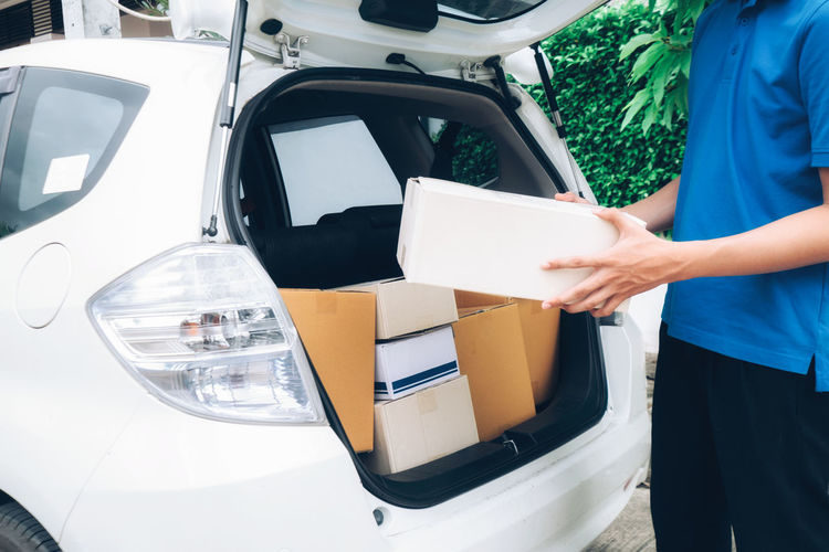 Midsection of delivery man holding cardboard box while standing at car