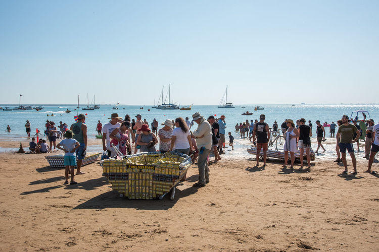 Darwin, Northern Territory, Australia-July 22,2018: Crowds on the Timor Sea coast with nautical vessels during the Beer Can Regatta at Mindil Beach in the NT of Australia Darwin Nautical Vessel Beer Can Regatta Event Festival Annual Event People Tourist Tourism Travel Travel Destinations Timor Sea Sea Ocean Shore Coast Shoreline Coastline Seascape Horizon Over Water Northern Territory Australia Leisure Activity Recreational Pursuit Fun Lifestyles Party Gathering Socializing Party - Social Event Beach Mindil Beach Large Group Of People Togetherness Friends Vacations Transportation Tropical Dusk Twilight Sunset Sky Beer Can Boat Sailboat Water Copy Space Arts Culture And Entertainment Women Young Adult