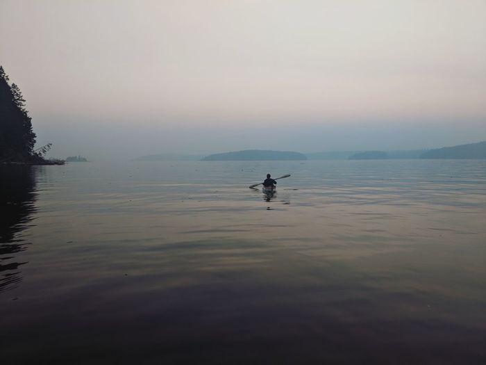 Man kayaking in lake against sky