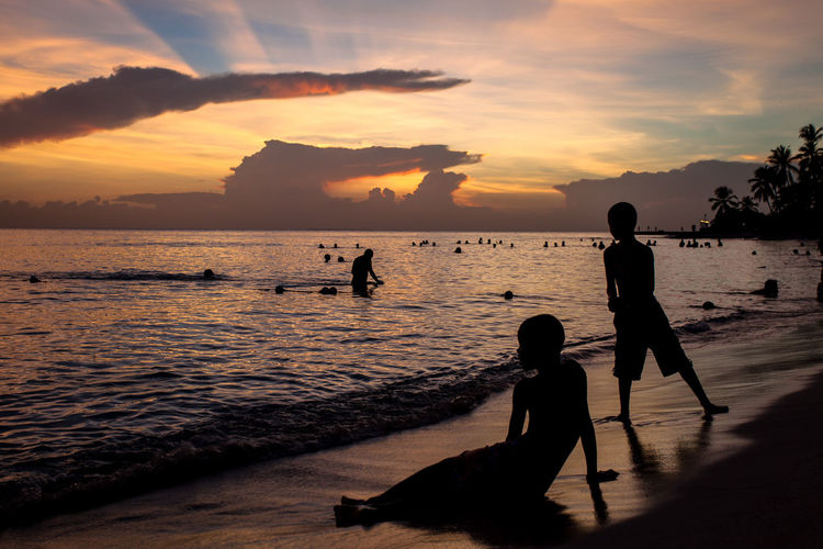 Silhouette Boys Walking At Beach Against Sky During Sunset