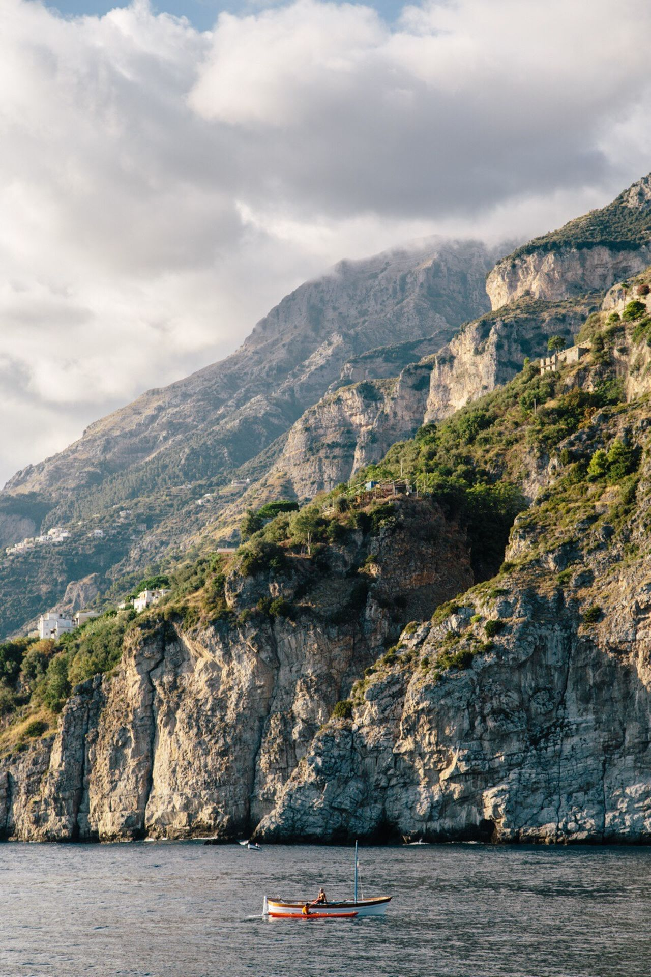 Scenic view of cliff against cloudy sky