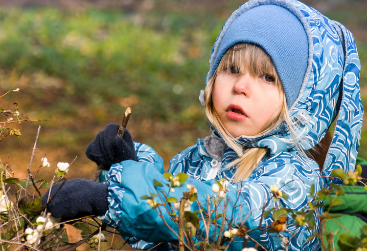 Portrait of cute girl wearing blue sweater holding plant in yard