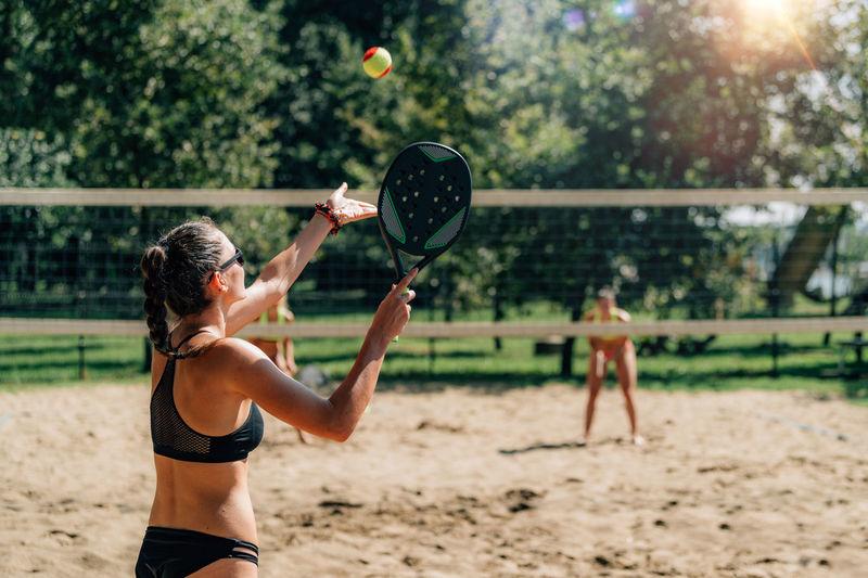 Female friends playing beach tennis