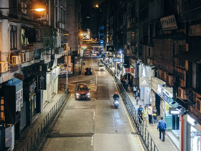 Traffic on city street amidst buildings at night