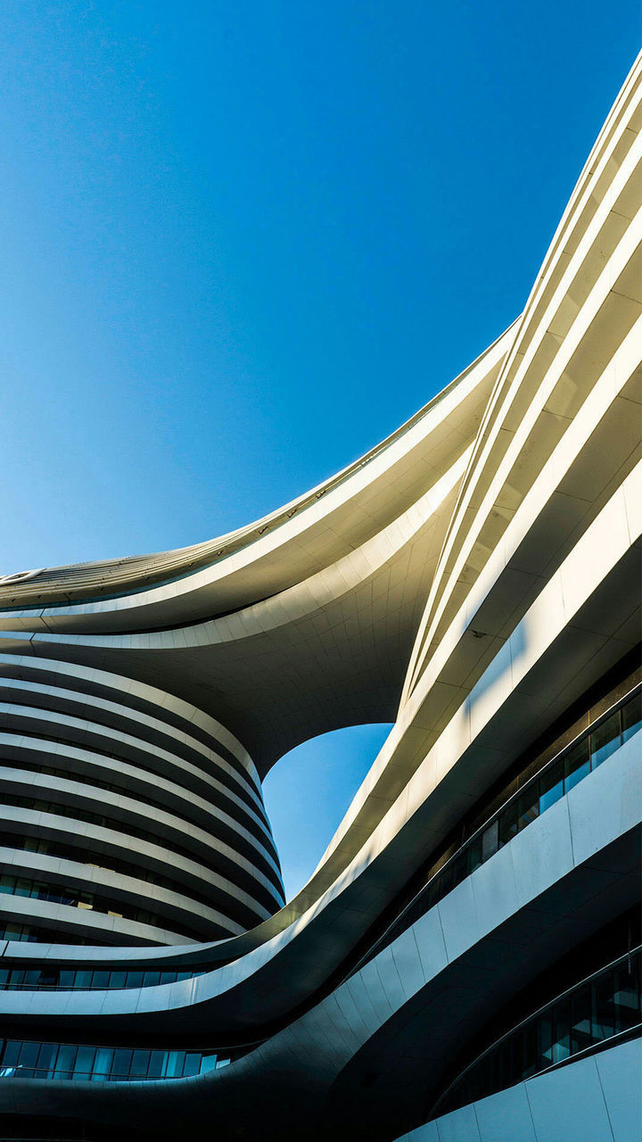 architecture, modern, built structure, abstract, futuristic, blue, clear sky, day, building exterior, curve, city, no people, low angle view, skyscraper, outdoors, steel, complexity, close-up, sky