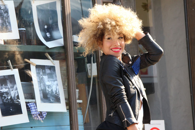 Smiling woman with curly hair standing in city on sunny day