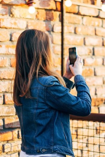 Side view of young woman photographing with mobile phone while standing by brick wall