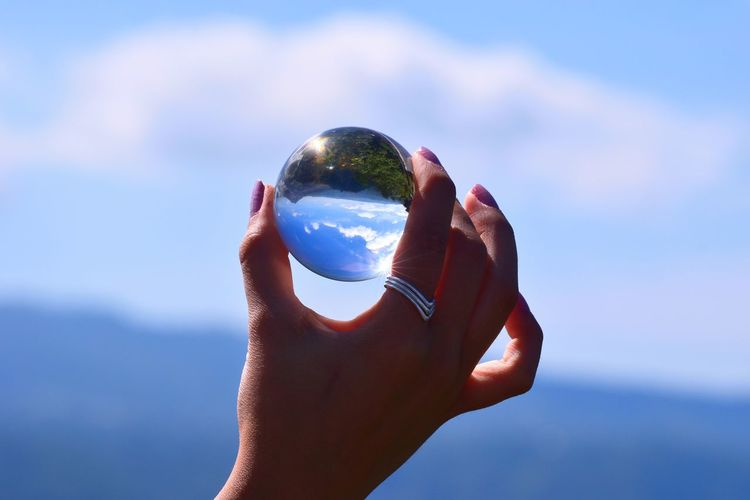 Midsection of person holding crystal ball against sky