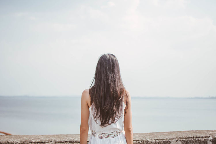 Alone Adult Adults Only Beach Horizon Over Water Leisure Activity Long Hair Nature One Person One Young Woman Only Outdoors People Real People Rear View Sad Sadness Scenics Sea Sky Standing Waist Up Water Women Young Adult Young Women