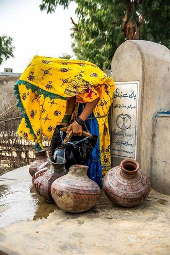 Woman Wearing Sari Filling Water In Pitchers