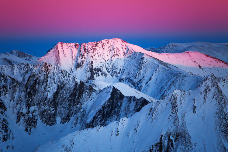 Scenic view of snow covered mountains during sunset
