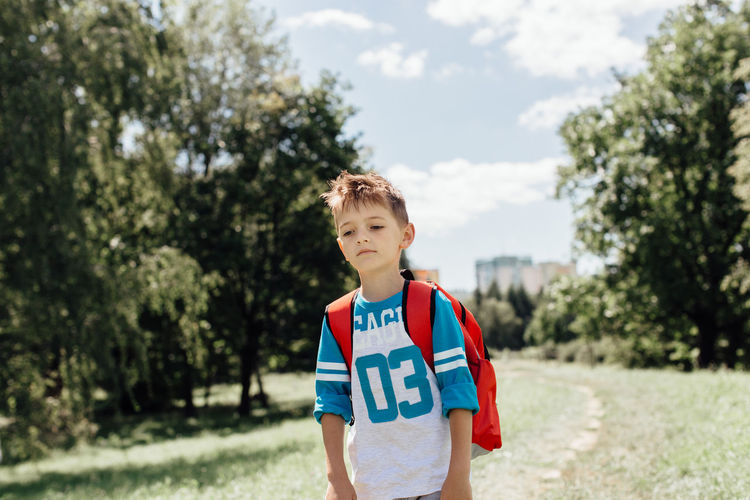 Portrait of a sad schoolboy on his morning way to school. 6 Years Alone Horizontal Miserable Red School Bag Unhappy Back To School Caucasian Child Childhood Copyspace Day Exhausted Front View Half Length Nature One Person Outdoors Real People Sad School Schoolboy Tree Upset