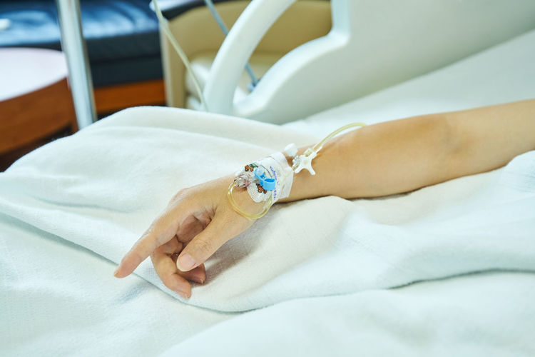 Cropped hand of woman with iv drip on bed in hospital