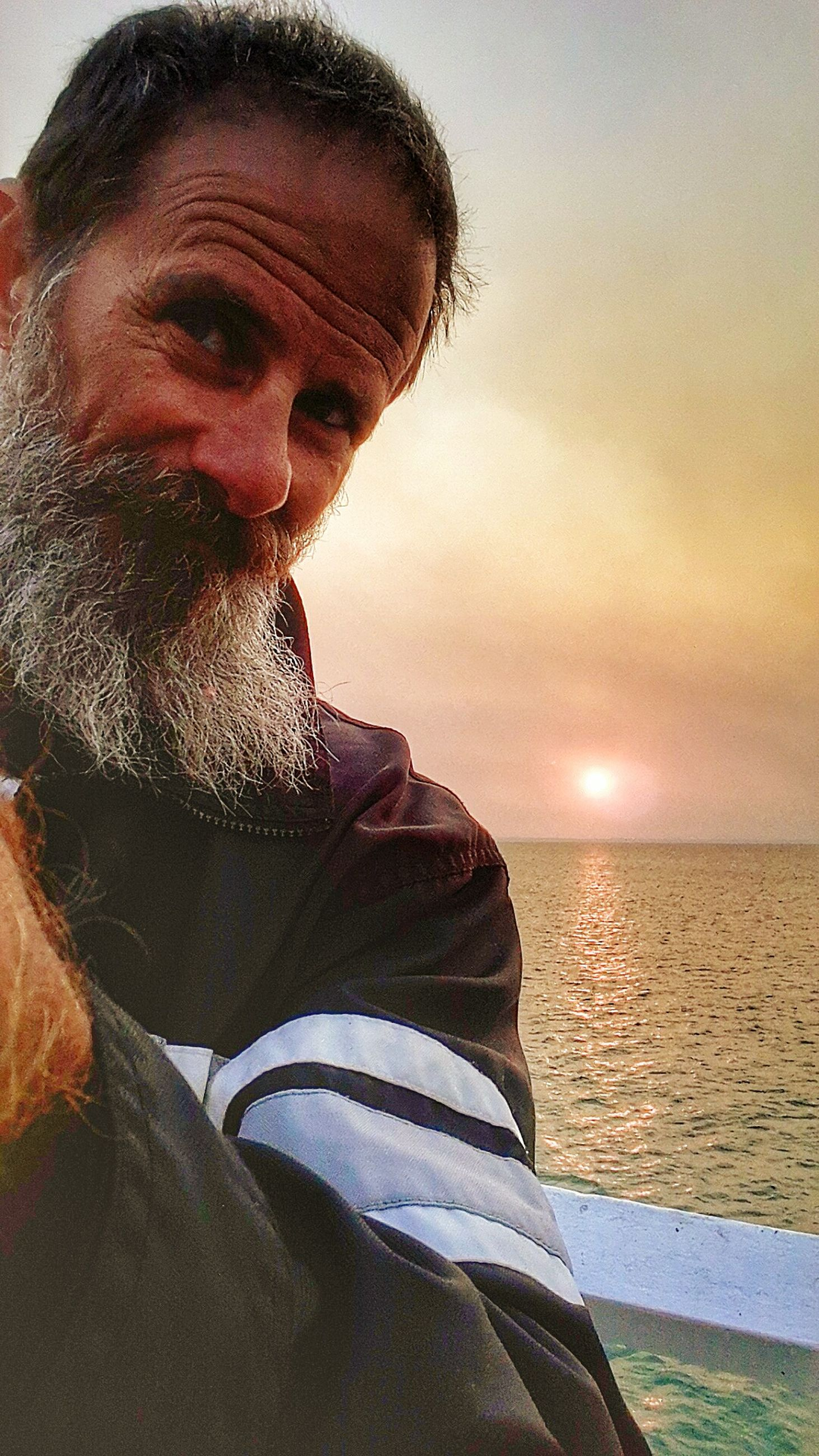 sea, one person, water, beard, real people, beach, horizon over water, leisure activity, nature, outdoors, mature men, scenics, lifestyles, sky, mature adult, beauty in nature, sunset, men, close-up, day, people