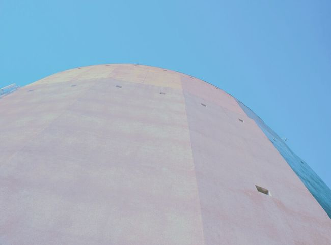 A rather wide, concrete tower. Modern Architecture Architecture Photography Architectural Design Building Exterior Architecture Concrete Architecture Concrete Wall Looking Up Blue Sky High Coloured No People Industrial Design Small Windows Geometric Architecture Geometric Shapes Simplicity Solid Colors Solid Blue Sky No Clouds Clean Photo Room For Text Wallpaper