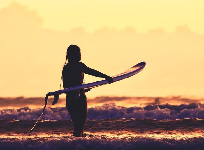 Silhouette woman with surfboard in sea against sky during sunset