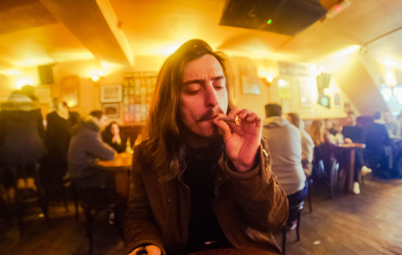 Young Man Smoking Marijuana Joint At Restaurant