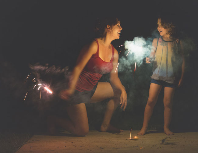 Happy mother and son with sparklers in dark