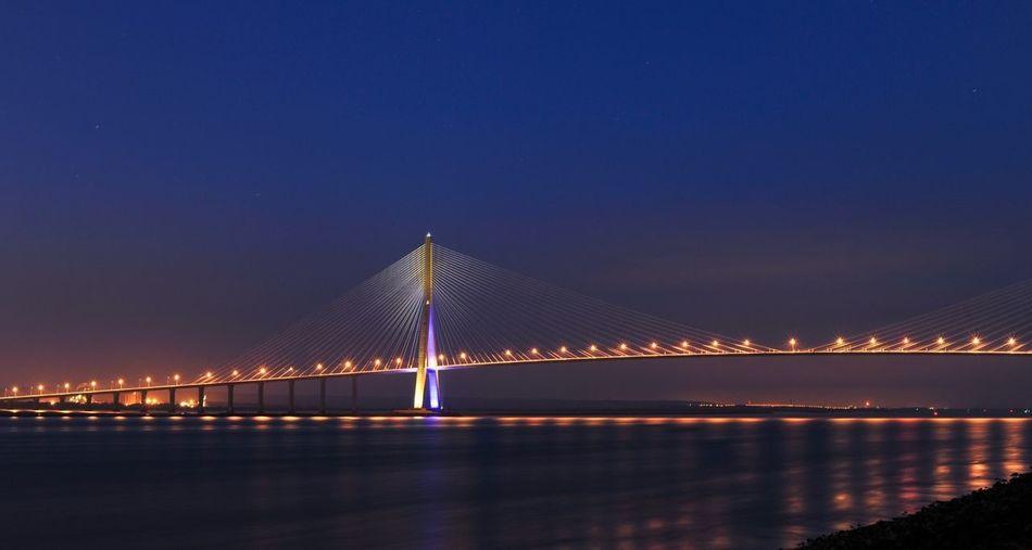 Illuminated bridge with reflection over water
