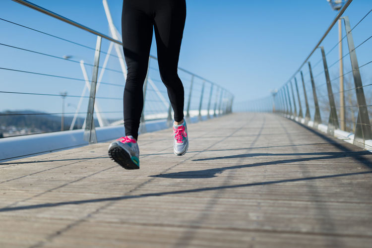 Low section of woman jogging on footbridge against clear sky