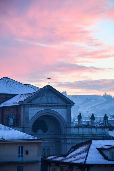 Snowed sunset in the city Winter City City View  Langhe Travel Destinations Winter Sunset Winter Tranquility Cityscape City Sunset Pink Sunset Building Exterior Church Facade Statues Beauty In Nature Hill Outdoor Travel City Snowed Roofs Snowed City Shades Of Winter