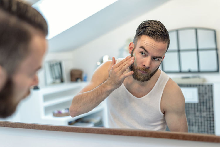 Young man applying facial cream while looking into mirror at home