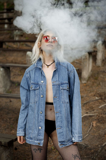 Portrait of young woman wearing sunglasses standing by smoke outdoors