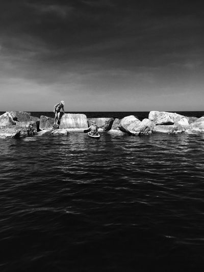 A man on breakwaters and a woman on the canoe The Week Of Eyeem The Week On EyeEm Your Ticket To Europe Beach Beauty In Nature Day Horizon Over Water Large Group Of People Leisure Activity Mix Yourself A Good Time Nature Outdoors People Real People Scenics Sea Sky Water Waterfront