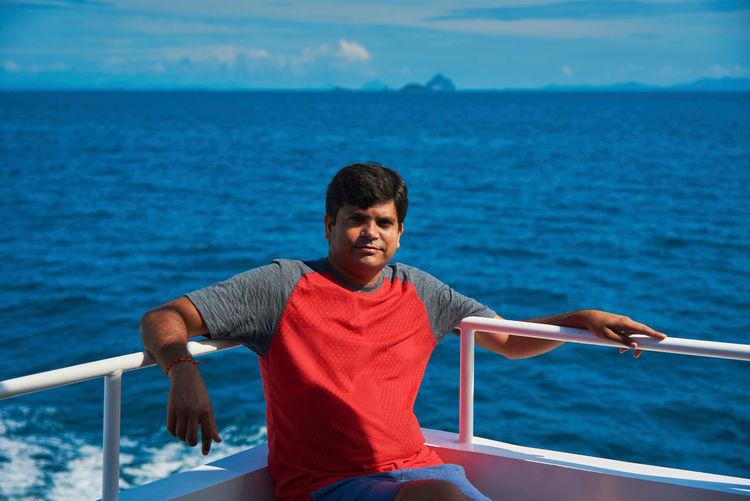 Portrait of man sitting on ship in sea