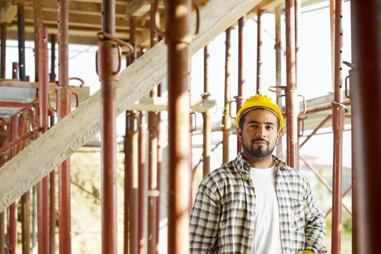 Portrait of young man standing at construction site