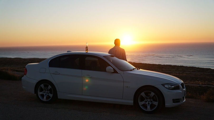 Side view of car on beach during sunset