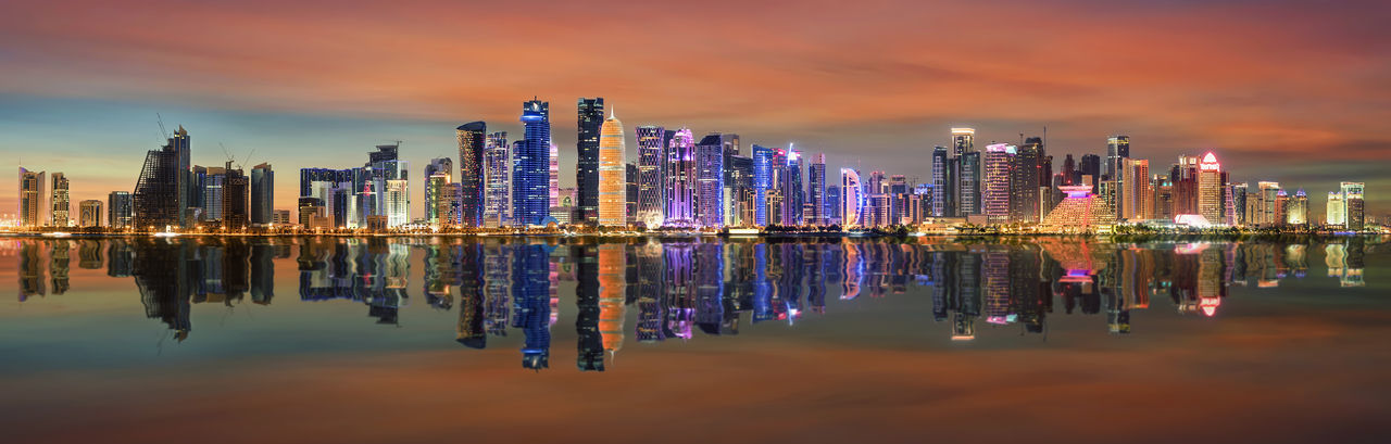 The modern skyline of Doha, Qatar, just after sunset Doha Middle East Arabic Architecture Building Building Exterior Built Structure City Cityscape Clouds Corniche Downtown District Financial District  Illuminated Modern Night Qatar Reflection Sky Skyscraper Sunset Tall - High Urban Skyline Water Waterfront