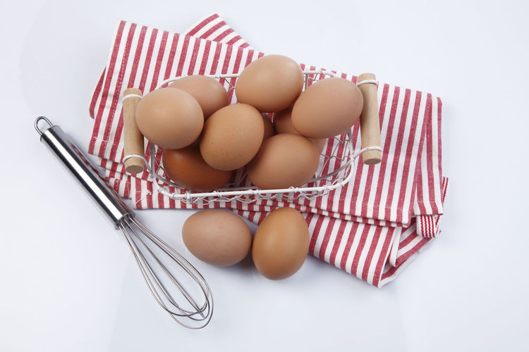 Close-Up Of Eggs In Basket Against White Background