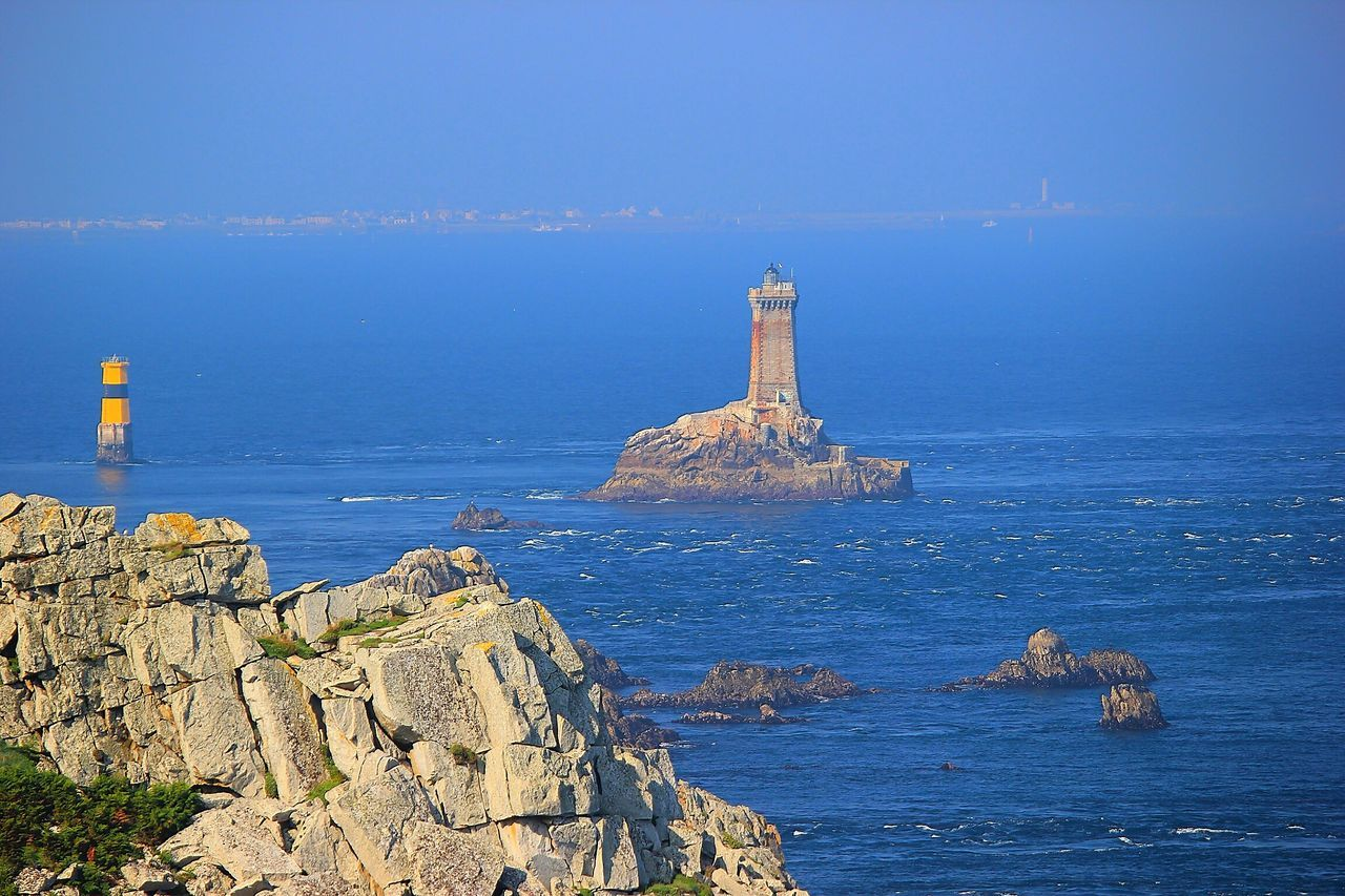 Lighthouse On Rock Formation At Sea Against Sky