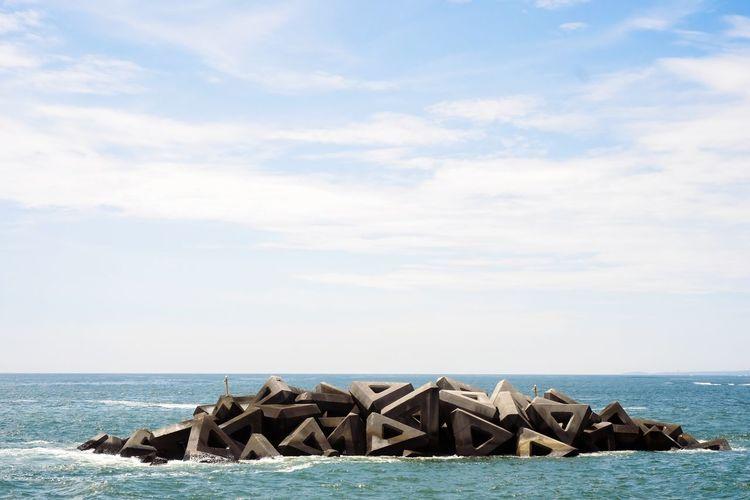Groynes Amidst Sea Against Cloudy Sky