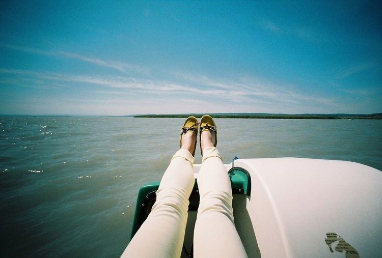 Low section of woman relaxing in pedal boat on lake against sky