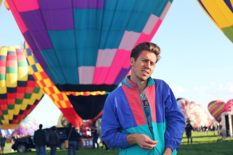 View of man standing against field of hot air balloons